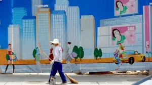 A worker in Beijing in front of a mural.